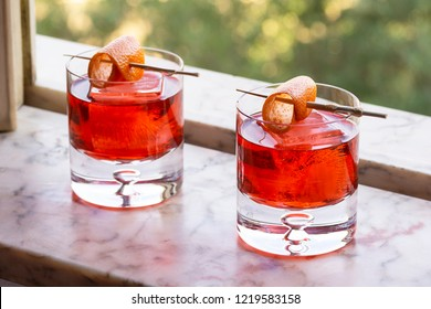 Classic Red Negroni Cocktails on Ice with Orange Twist on Marble Windowsill