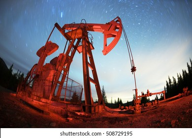 Classic retro Oil pump under the stars on the mountain with illuminated Synechka Oil  gas production in Ukraine an old ancient method of producing hydrocarbons  chemical raw materials