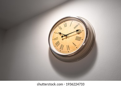 A classic round clock with roman numbers which is installed on white plain wall. Interior decoration object photo. Close-up and selective focus at some part of the clock.