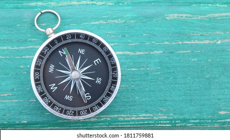 Classic round compass on green wooden vintage background as symbol of tourism with compass, travel with compass and outdoor activities with compass