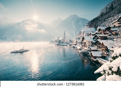 Classic scenic postcard view of famous Hallstatt lakeside town in the Alps with passenger ship on a beautiful cold sunny day with blue sky and clouds in winter, Salzkammergut region, Austria