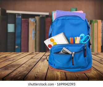 Classic school backpack with colorful school supplies and books on desk.