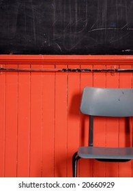Classic school chair with black board in the background with red painted wood paneling