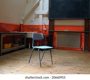 A classic school chair in the middle of an empty classroom with desks and black-board