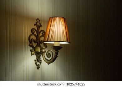 Classic sconce with turned on bulb under lampshade hanging on wall.