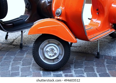Classic scooter. Orange print Piaggio Vespa parked on a public street in Italy. Vintage scooter wheel and body design details.Treviglio Lombardy Italy. July 2, 2016