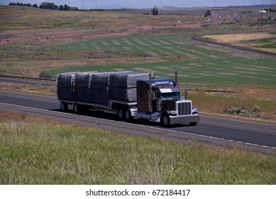 A Classic Semi-Truck pulls a loaded flatbed down a rural US Highway. June 20th, 2017 Oregon, USA