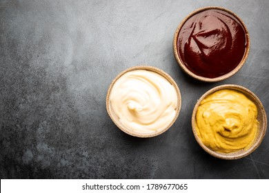 Classic set of sauces, American yellow mustard, ketchup, barbecue sauce, mayonnaise on black stone background, top view with copy space.