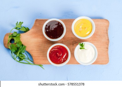 Classic set of sauces in white saucers: American yellow mustard, ketchup, barbecue sauce, mayonnaise. On cutting board light blue stone concrete table top view, copy space