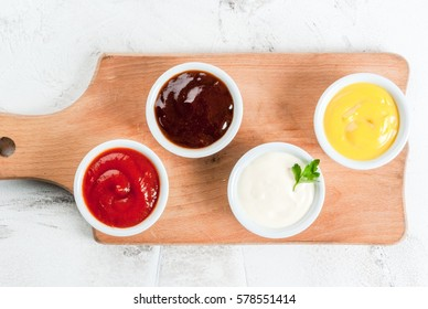 Classic set of sauces in white saucers: American yellow mustard, ketchup, barbecue sauce, mayonnaise. On cutting board white stone concrete table top view, copy space