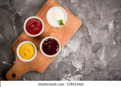 Classic set of sauces in white saucers: American yellow mustard, ketchup, barbecue sauce, mayonnaise. On grey black spotted concrete stone table top view, copy space.