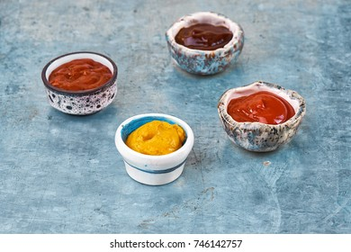 Classic set of sauces in white saucers: American yellow mustard, ketchup, barbecue sauce. On grey black spotted concrete stone table top view, copy space. bowls of various dip sauces, top view