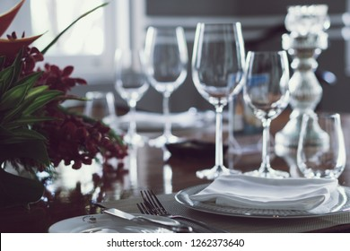 Classic setting traditional fine dining table elegant luxury style with silverware, wine glass, flower on special occasion date, family toast wedding party, anniversary, thanksgiving, christmas dinner