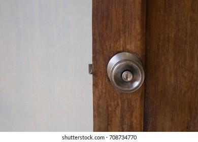 classic silver door knob on ancient wooden door with grey space wallpaper behind the door