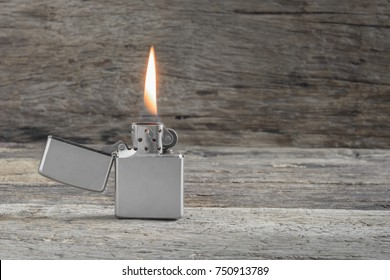 classic silver metal lighter with flame on old and crack wooden surface, copy space for text