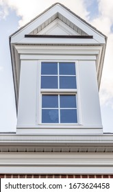 Classic single dormer window with decorative triangle trim, double hung sash window, above a white ventilating soffit roof line on a new construction American single family real estate property