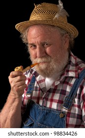 Classic smiling senior farmer with straw hat, plaid shirt, bib overalls, and corn cob pipe. Vertical layout, isolated on black background with copy space.