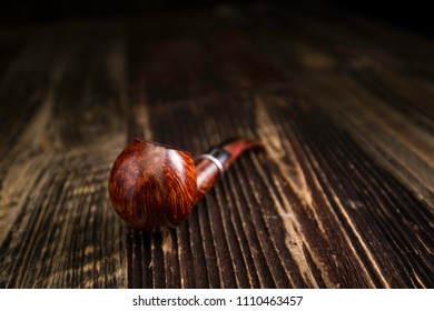 Classic smoking pipe on a rustic wooden table