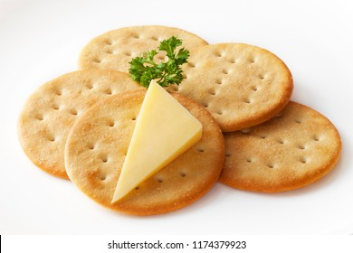 Classic snack, cheddar cheese and crisp crackers on a white plate garnished with parsley. Clipping path included.