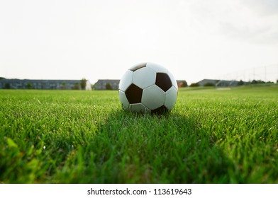 Classic soccer ball in the grass field at dusk, great copy space above