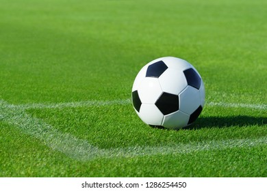 A classic soccer ball lies on the bright green grass on the football field in the designated area of the penalty area at a sports stadium close-up in a large sports center for football players
