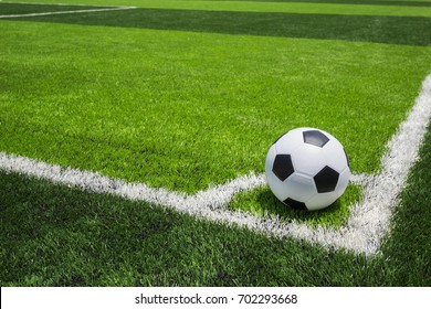 Classic soccer ball on artificial bright and dark green grass at public outdoor football or futsal stadium