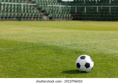 Classic Soccer Ball on Stadium Field. Row of Seats in the Stadium in the Background. Football Arena Seating Area in the Background. Grass Football Pitch