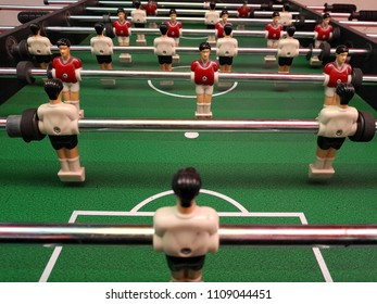 classic soccer game table, toy players in white and red uniforms