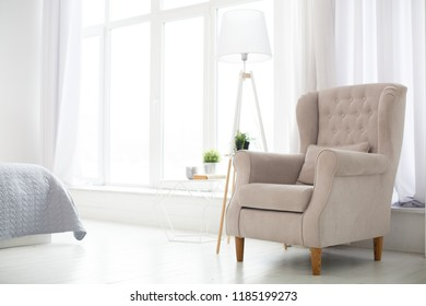 Classic soft armchair near the window in a room. Classic simple interior