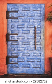 Classic spanish style painted blue wooden door with metal handle