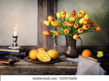 Classic still life with bouquet of tulips flowers placed with fresh oranges, scarf,vintage books and illuminated candle on rustic wooden table.