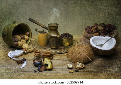 Classic still life with fresh coconut fruit placed with jute bag full of chestnuts, copper tray with hot cup of coffee and roasted coffee beans, cinnamon, and nuts on rustic wooden table.