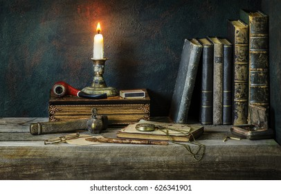Classic still life with vintage books placed with illuminated candle,old pipe,copper box,pocket watch and old inkwell on rustic wooden background