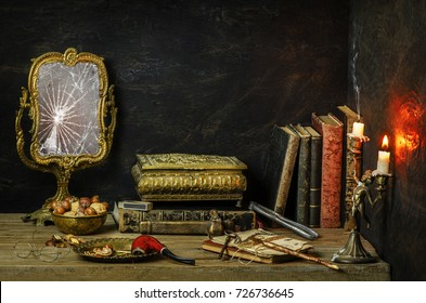 Classic still life with vintage books placed with old broken mirror,antique candlestick,pipe,nuts and old glasses on rustic wooden background