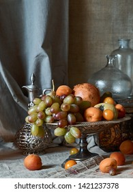 A classic still-life in the Dutch old masters style with fruits on a silver, platter and silver carafe.  With draperies on a gray canvas background.