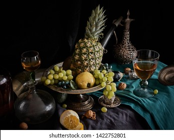 A classic still-life in the Dutch old masters style with pineapple and  grapes, on a silver, platter. Silver carafe. on a gray and blue canvas in the background.