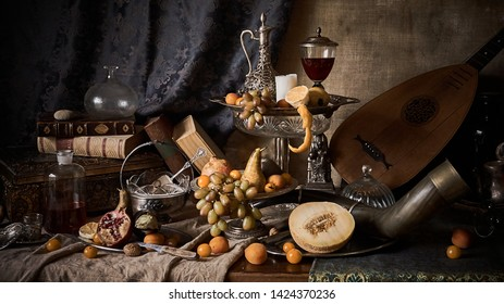 A classic still-life in the Dutch old masters style with fruits on a silver, platter, silver carafe.  old books , glass of wine, hunting horn and guitar lute .