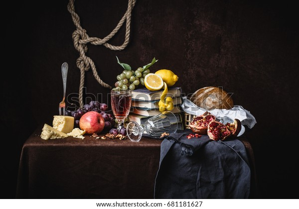 A classic still-life in the Dutch style with fruit cheese and books. On a dark brown background. With draperies