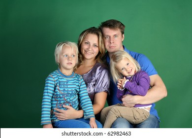 Classic Studio Family Portrait of four. Smiling mommy, daddy, funny cute daughter and 5 years dreaming boy