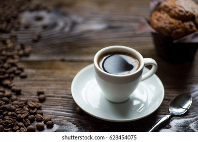 Classic style espresso shot with chip muffin and coffee beans on old wooden table.