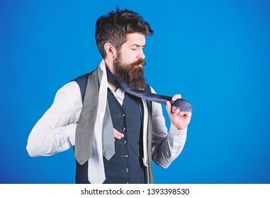 Classic style. How to match necktie with shirt and suit. Man bearded hipster hold few neckties on blue background. Guy with beard choosing necktie. Gentlemens guide. How to choose right tie.