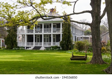 Classic summer home with a large porch and a wooden swing