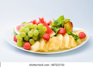 classic summer Italian food. Beautifully decorated fruit platter with watermelon, melon, apricot and grapes on a white plate, light background