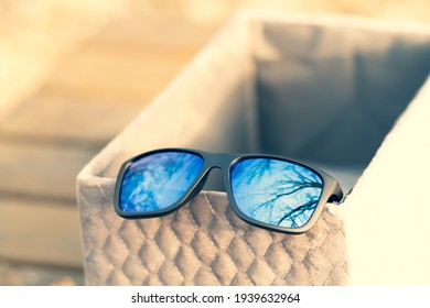 Classic Sunglasses with blue lenses shoot outside in a summer day closeup. Selective focus