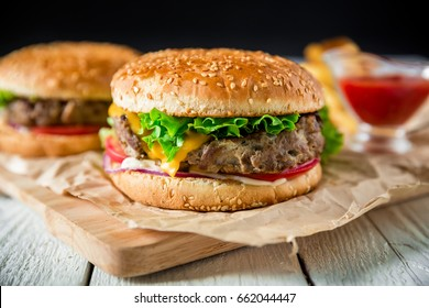Classic tasty hamburger with beef, sauce and french fries on dark background. American food