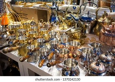 Classic teapots and saucepans with handles for sale at the Dubai market.