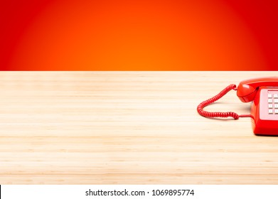 Classic telephone on right corner of wooden desktop, old red telephone  on red and orange background. Concept of Hotline, Contact, Customer service