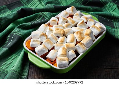 Classic thanksgiving dish loaded sweet potato casserole with the marshmallow on top, on a wooden cutting board with a green kitchen dish towel on rustic wooden table, horizontal, close-up
