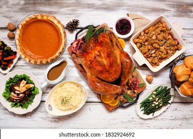 Klassisches Thanksgiving-Truthahn-Abendessen. Draufsicht, Tischszene auf rustikalem weißem Holzhintergrund. Türkei, Kartoffelbrei, Kuchen, Kürbiskuchen und Seiten.