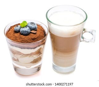 Classic tiramisu dessert with blueberries in a glass and cup of coffee isolated on a white background with clipping path